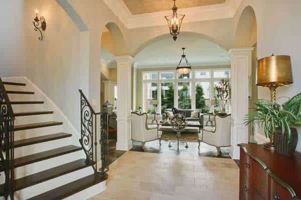 This foyer has a carved console table topped by a brass lampshade and a living room that's framed with open archways.