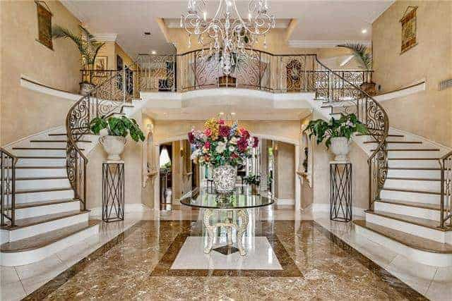 This fancy foyer is filled with a round circular table in the middle, luxurious chandelier and flower pedestals sitting against the bifurcated staircase.
