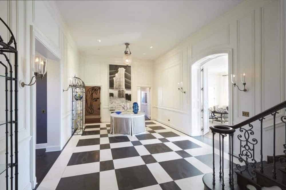 This elegant entry foyer features a checkered tile floor, white walls, round table in the middle and white ceiling.