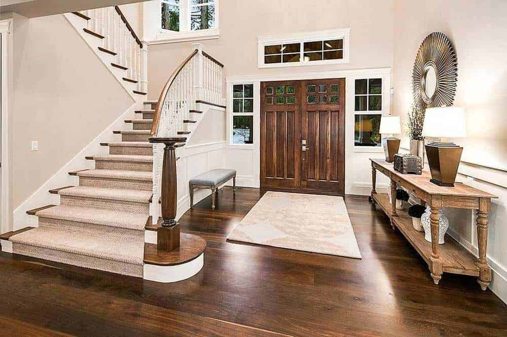 This foyer has a dim hardwood flooring differentiated by a beige zone carpet flanked by a padded seat on one side and a wooden comfort table on the other.