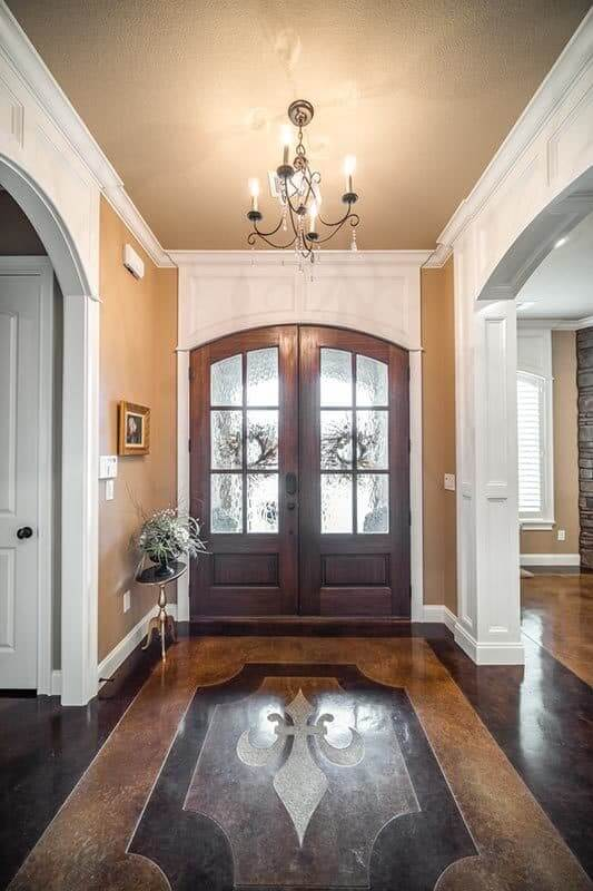 The foyer has a wooden french entryway and a candle crystal chandelier hanging over the brightening flooring.