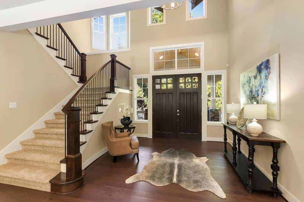 The dark wooden main door of this home has exquisite glass boards on its sides or more to enlarge the transom window of the tall roof expecting to light up the anteroom with normal lighting
