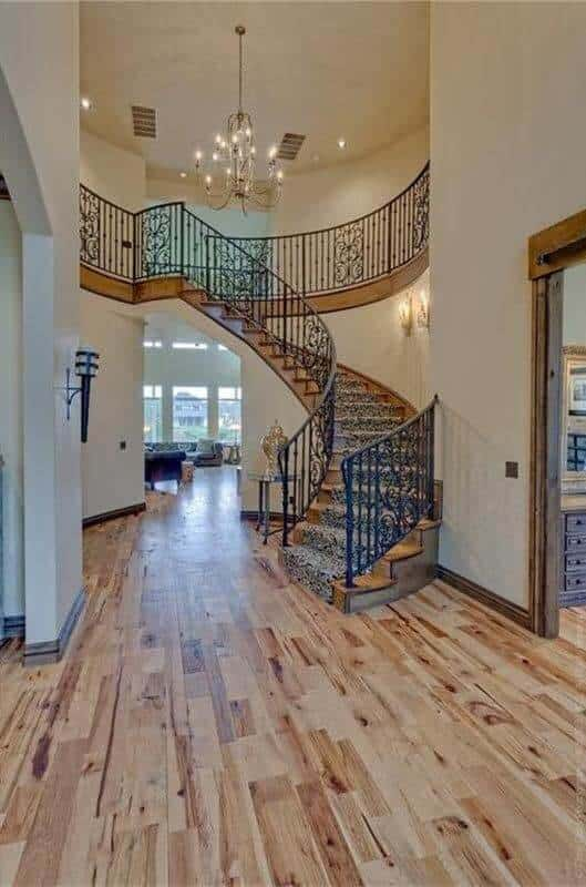 This foyer features an elaborate staircase dressed in a patterned carpet and light hardwood flooring and a winding staircase illuminated by a candle chandelier.