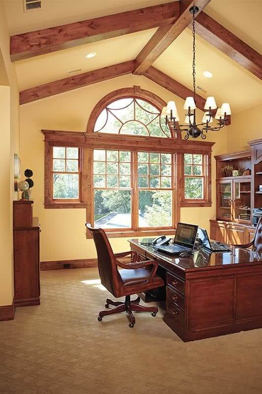 This home office with a high vaulted ceiling with exposed wooden beams and wooden desk paired with comfy seats.