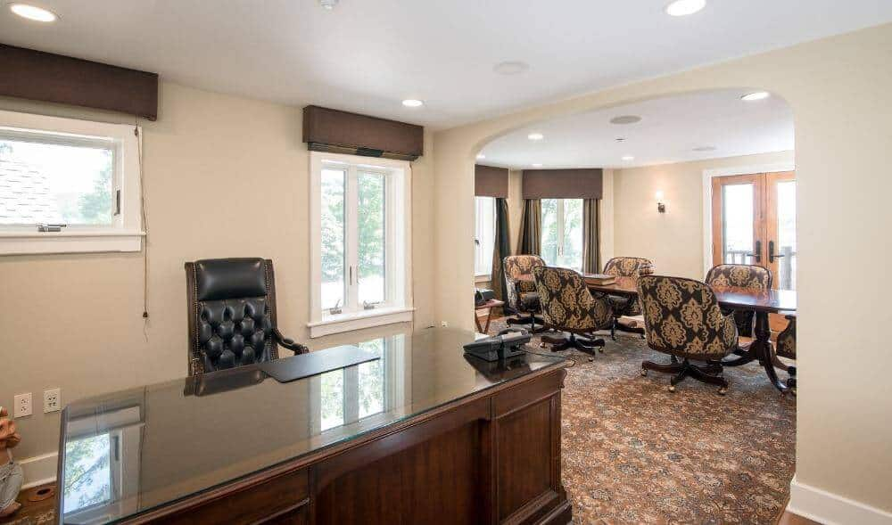 This home office with a work area and seat set, alongside a multi-utilize oval-formed table combined with modern seats on the room.