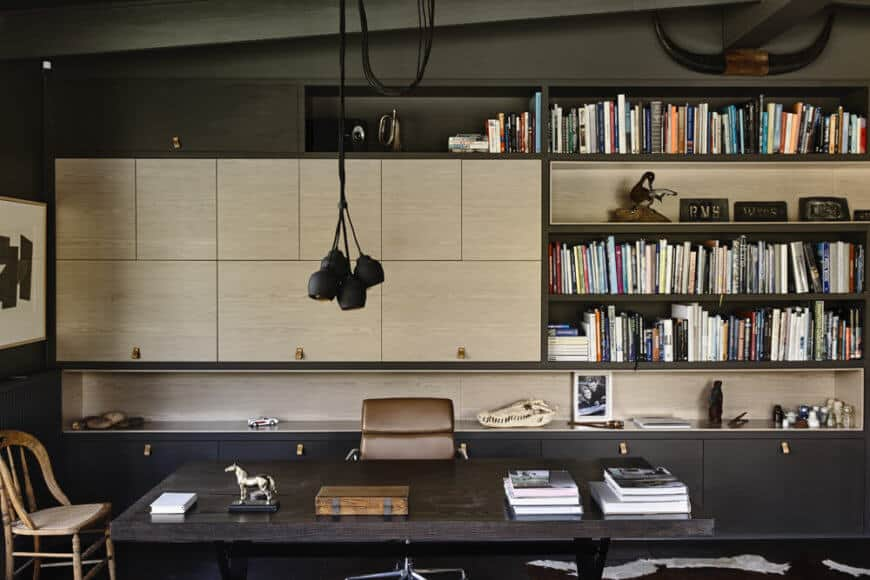A home office was an important part of the design, a space rife with sleek cabinetry and shelving, centered on a large dark wood desk. The appearance of a light toned wood offers a slight break from the prevailing style.