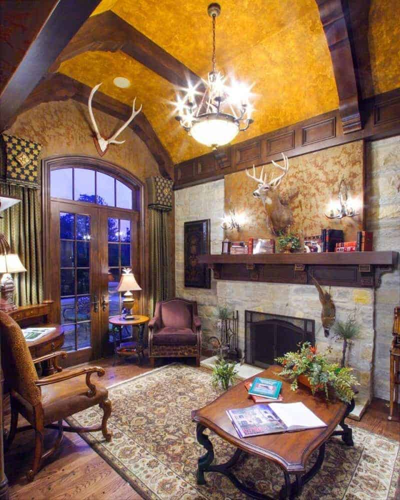 This room has a couple of leather armchairs in close proximity to the large stone fireplace. It also has a classic rug lit by a stunning chandelier.
