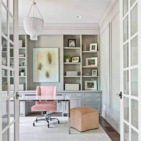 A home office with a white ceiling mounted with a stunning chandelier and chrome desk paired with a pink office chair.