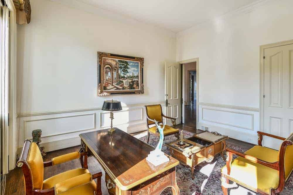 The charming home office has a classic vibe to its covering, wooden old fashioned work area and charming armchair over the designed carpet flooring.