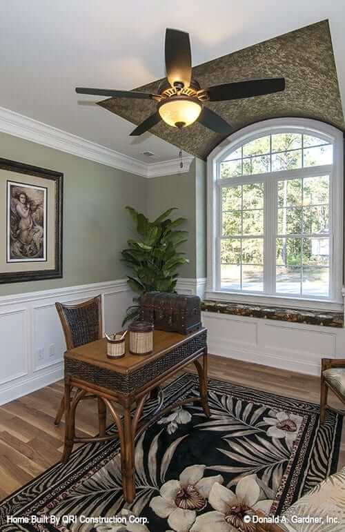 Home office with green and white wainscoted walls, curved windows, and hardwood flooring bested with a dark flower mat.
