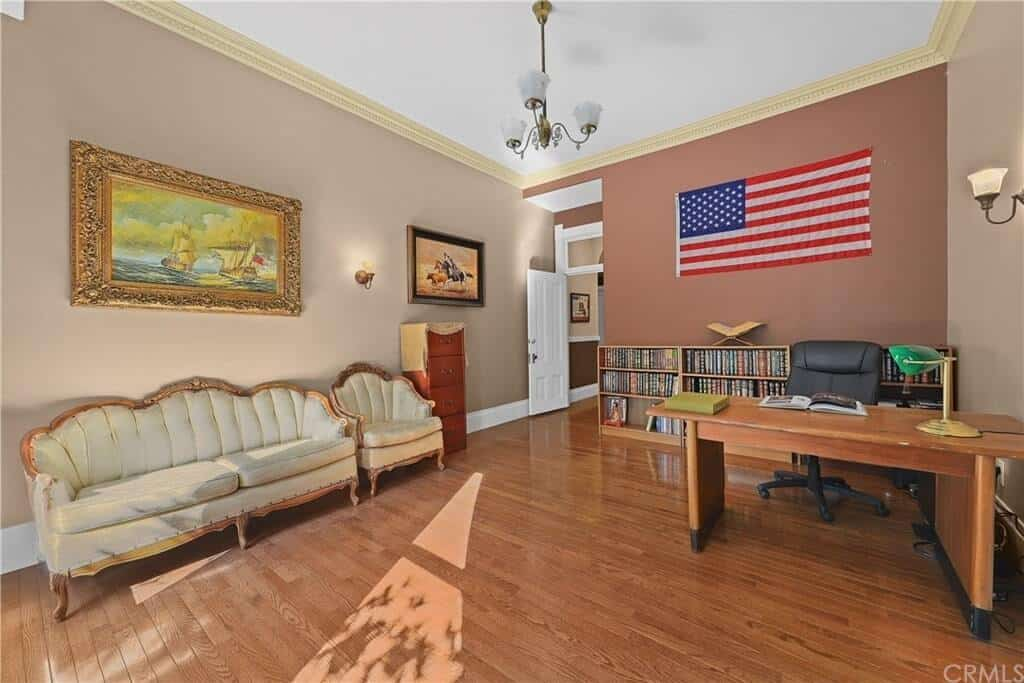 This home office has a wooden table paired with an office chair on the hardwood flooring. It also has a cozy sofa and paintings on the walls.
