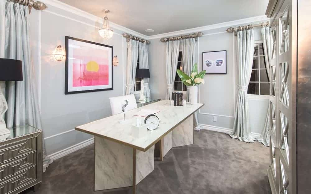 The home office has a huge white marble work area that contrasts the light-dark walls and dim covered ground surface that matches the silver cabinets.