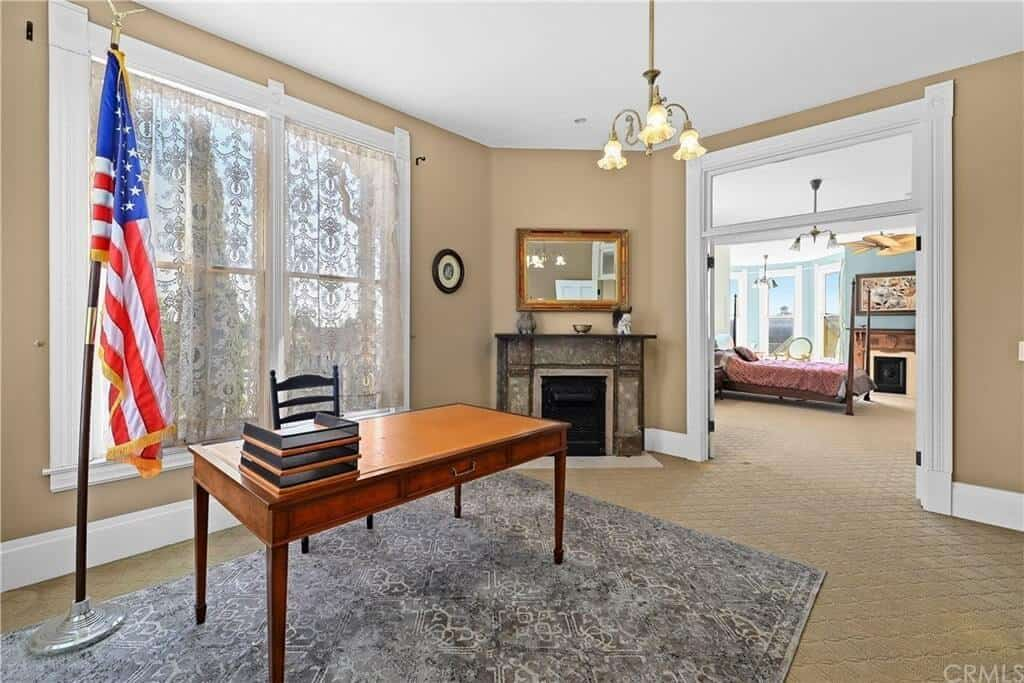 This charming office home features a wooden table and chair on the rug. It also has fireplace and a door that leads to the primary bedroom.