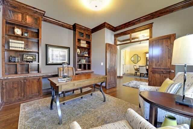 This home office with a wooden desk on the classic rug and wooden built-in shelves matches the hardwood flooring.