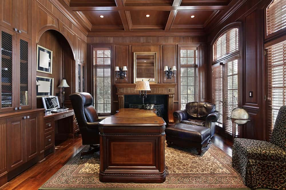 Luxury home office with coffered ceiling, windows, and a fireplace.