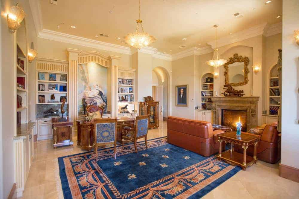 The charming den and home office of the mansion has an antique wooden desk paired with beautiful chairs. Beside this is a leather couch facing the large fireplace that is adorned with an elegant wall-mounted mirror above it.