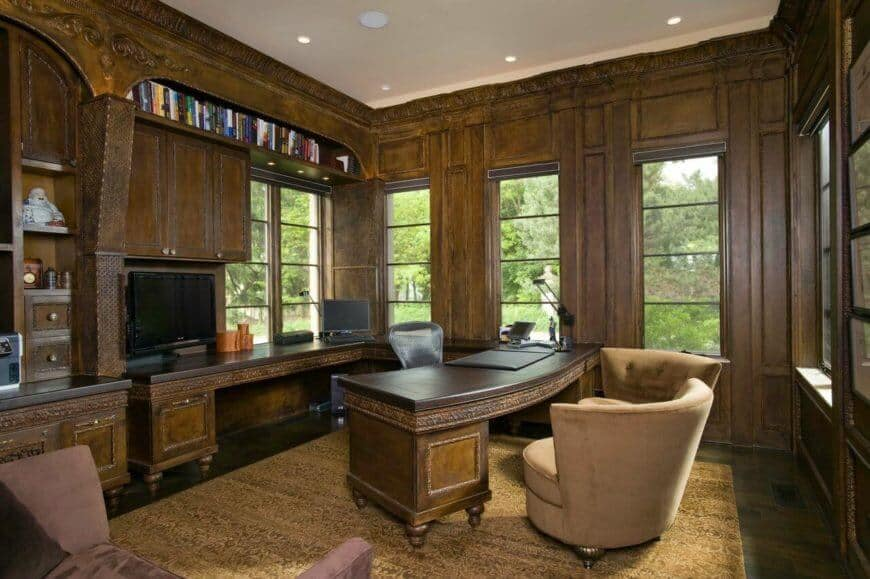 The elegant home office has lovely crown molding, paneling, and built-in desks. A matching curved desk extends from the back wall into the center of the room.