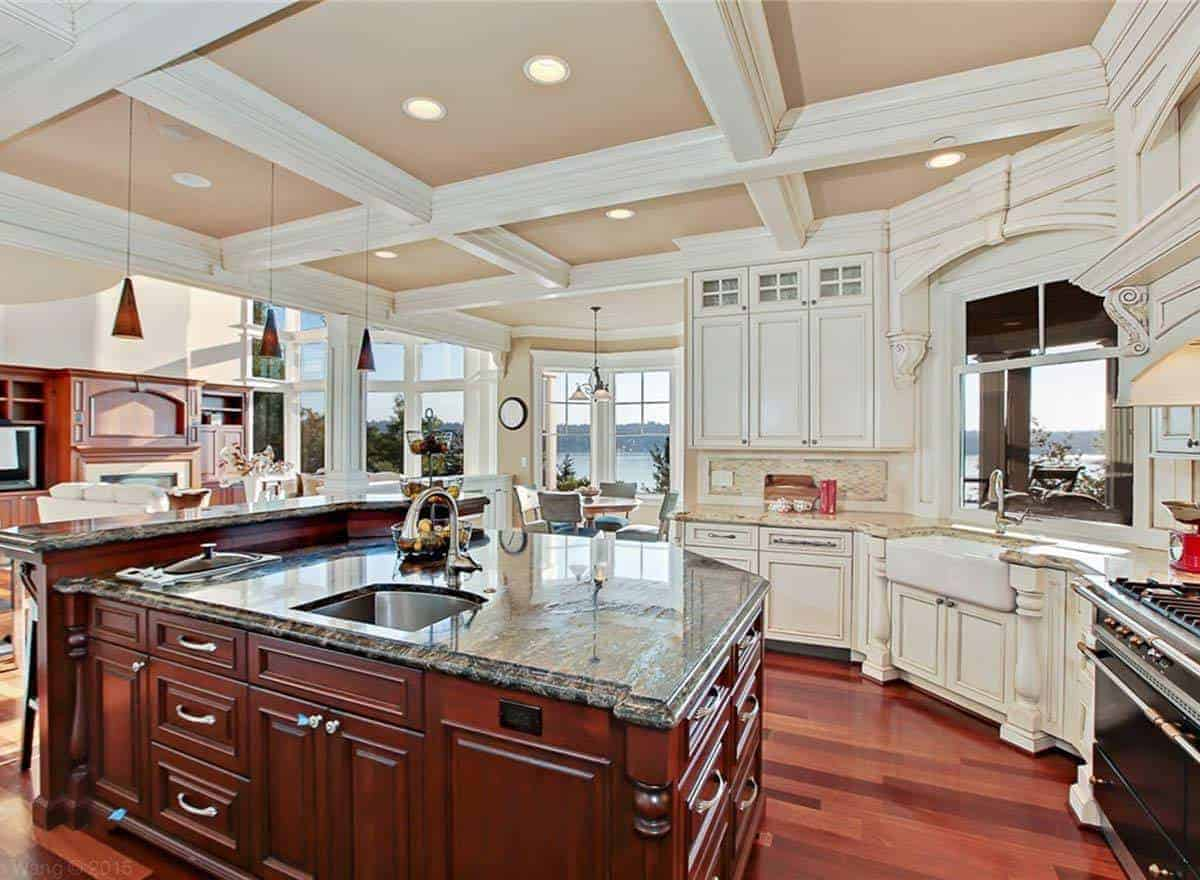 This kitchen features a gorgeous coffered ceiling and rich hardwood flooring. It also has a granite top peninsula and counter.