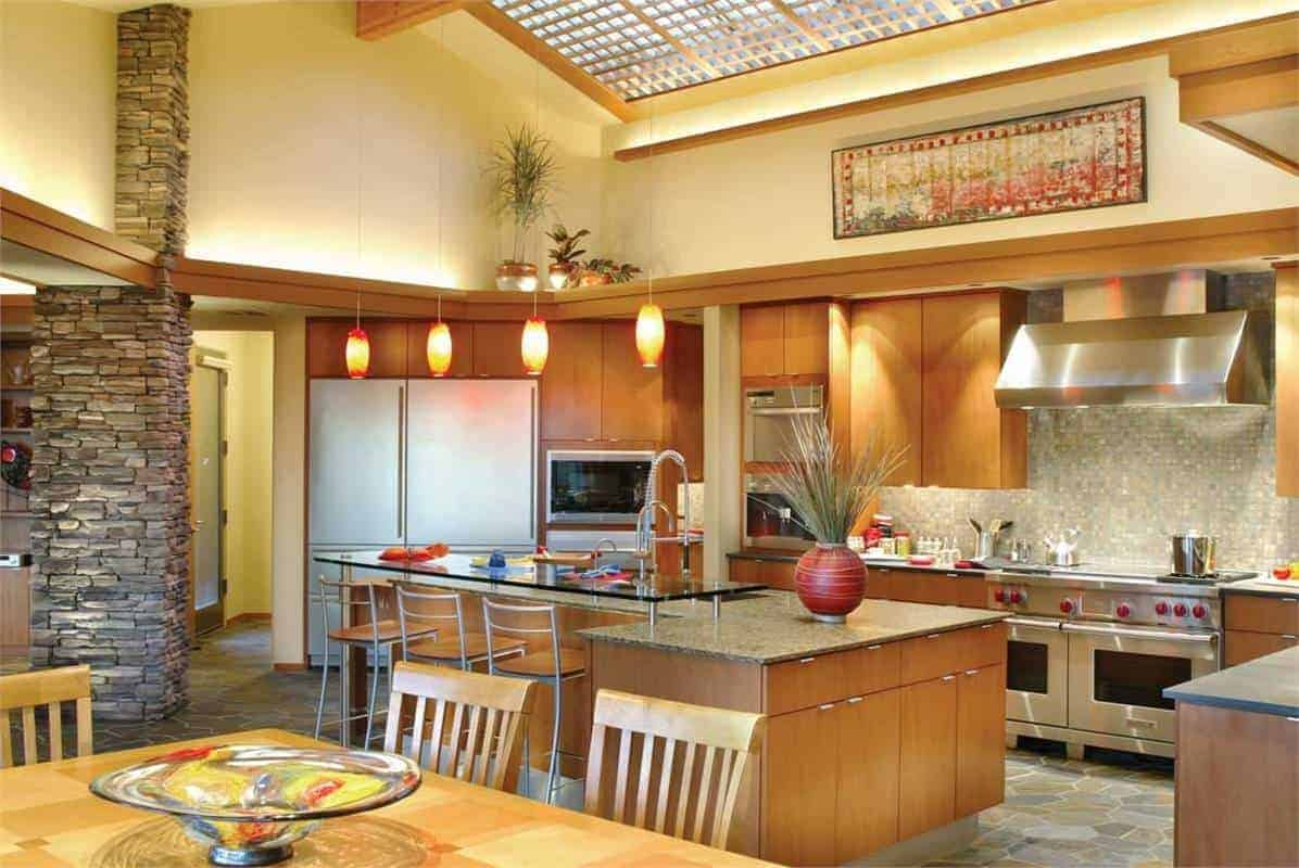 This kitchen area features a skylight framed by wooden trims and stainless steel appliances and an L-shaped kitchen island.