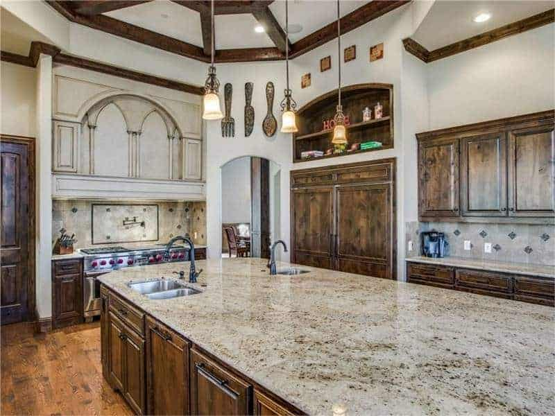 This kitchen has an attractive tray ceiling styled with wooden ceiling beams and marble top kitchen island that matches wooden cabinetry.