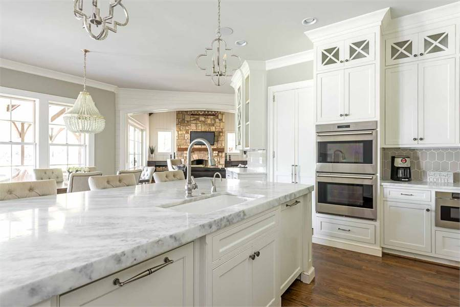 This white kitchen features a marble countertop and white cabinetry in addition to stainless steel appliances.