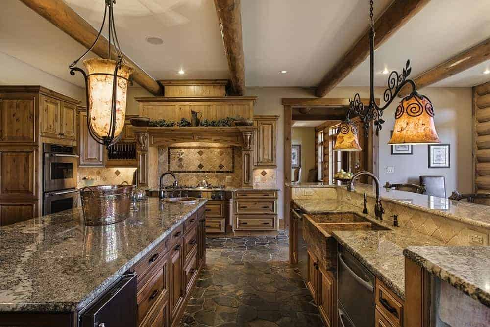 The gorgeous kitchen has the same wooden tone and details as the rest of the log cabin. It has various wooden cabinetry and a galley-style aesthetic with counters topped by charming lamps.