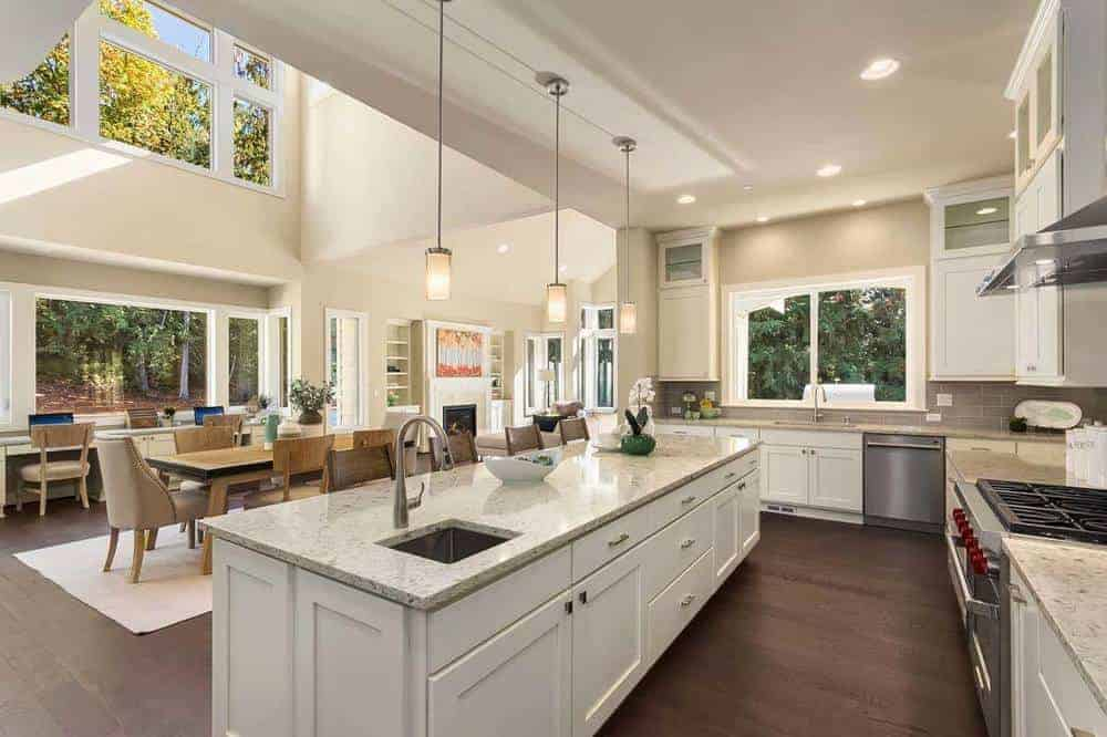 This kitchen area offers a kitchen island with white cabinetry lit by lovely pendant lights. The kitchen contrast the dark hardwood flooring.