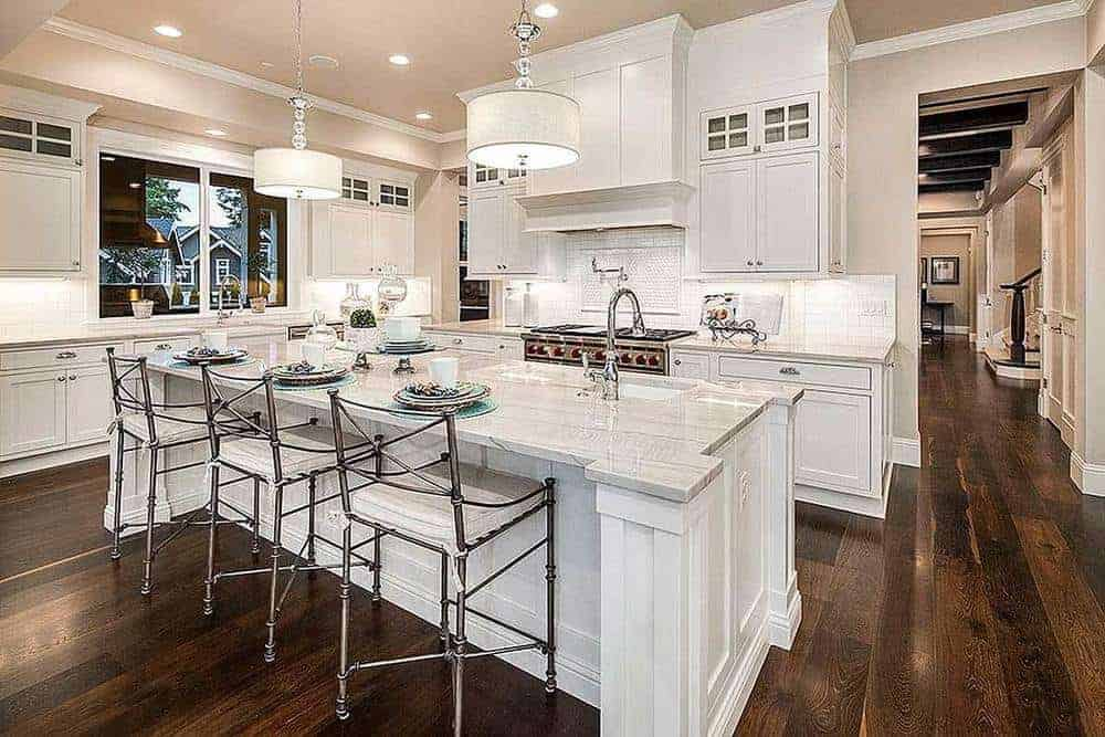 This kitchen has an enormous white kitchen island that additionally serves as the breakfast bar enlightened by couple pendant lights swinging from the beige roof that likewise has recessed lights.