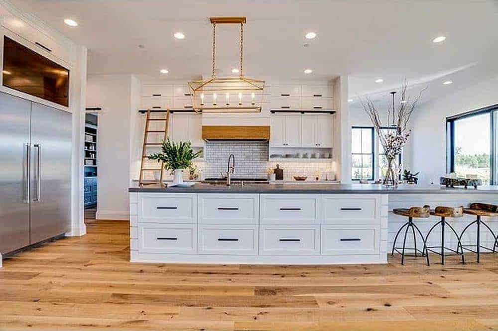 This kitchen area features a large white kitchen island standing out against the hardwood flooring with its bright white cabinetry.