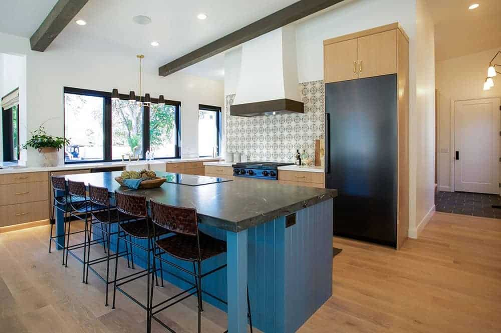 This kitchen area has a hardwood flooring that makes the matte blue wooden kitchen island stand out in the center.
