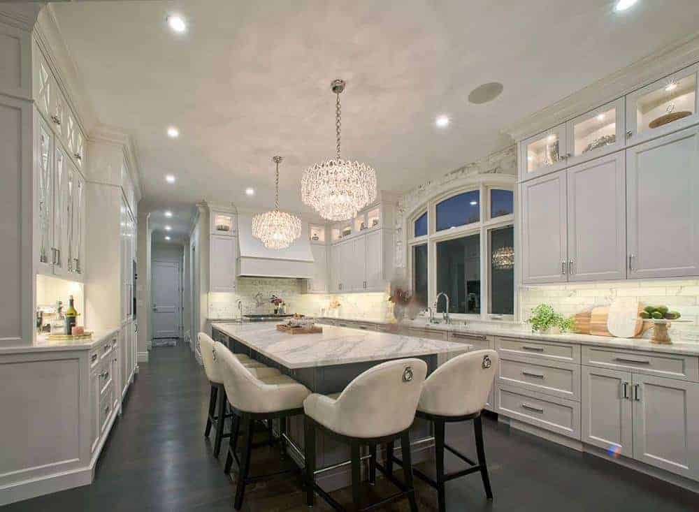 This charming kitchen area features a couple of large crystal chandeliers hanging over the immense kitchen island.