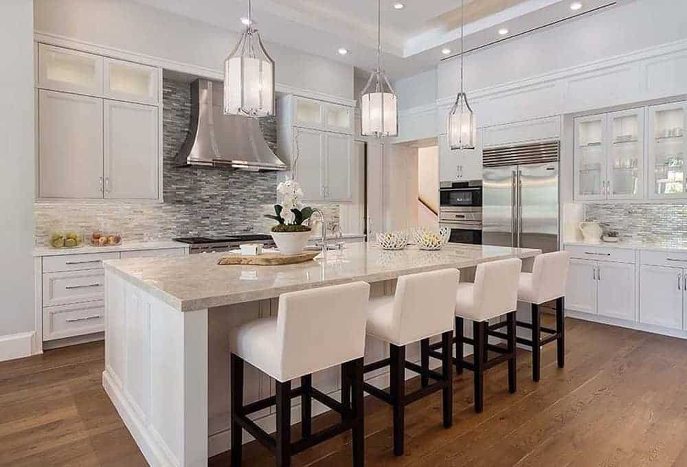This elegant kitchen area features a beige countertop of the kitchen islands pairs well with the beige cushioned stools for the breakfast bar.