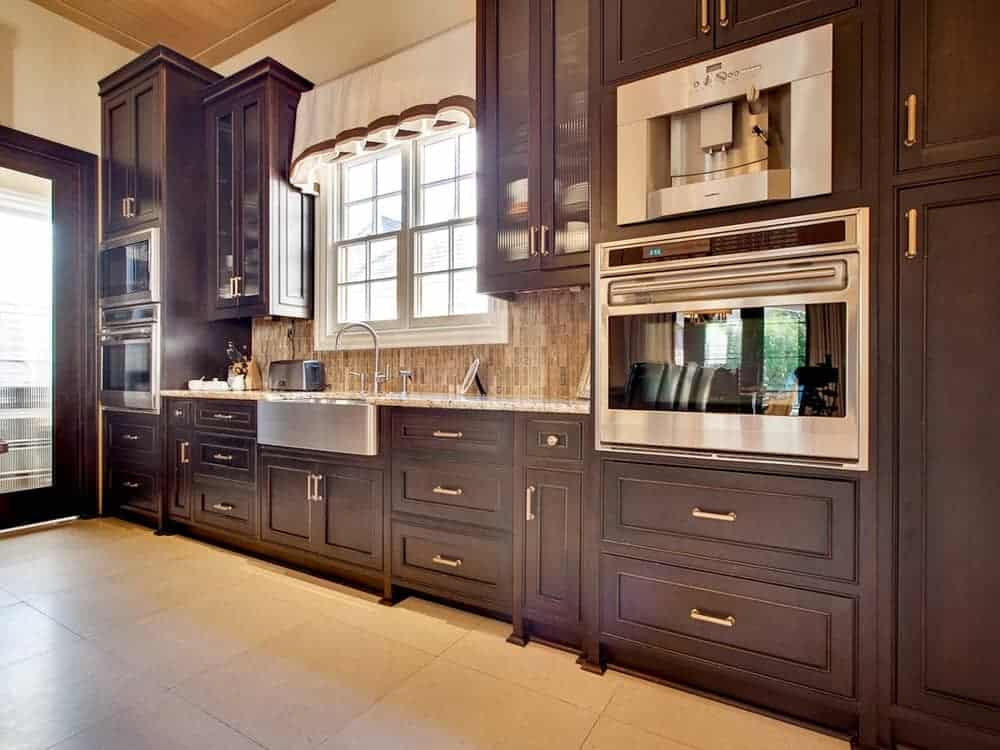 This kitchen features dark brown cabinetry that making them contranst the beige flooring and stainless steel appliances.