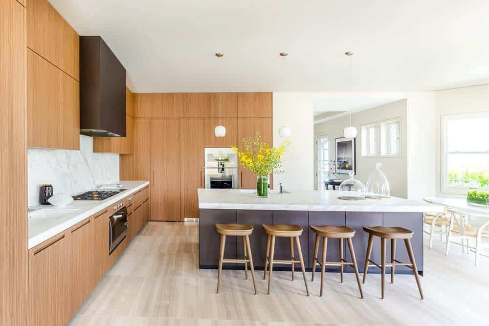 The charming kitchen of this mansion has light tones on its flooring to match the walls and ceiling complemented by the wooden cabinetry lining the walls.