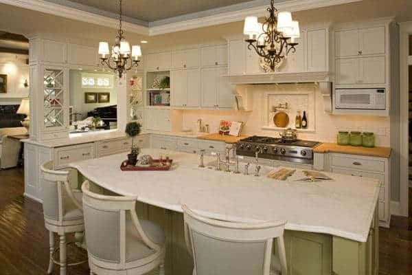 This kitchen offers a marble top kitchen island brightens by ornate chandelier and it also has white cabinetry.