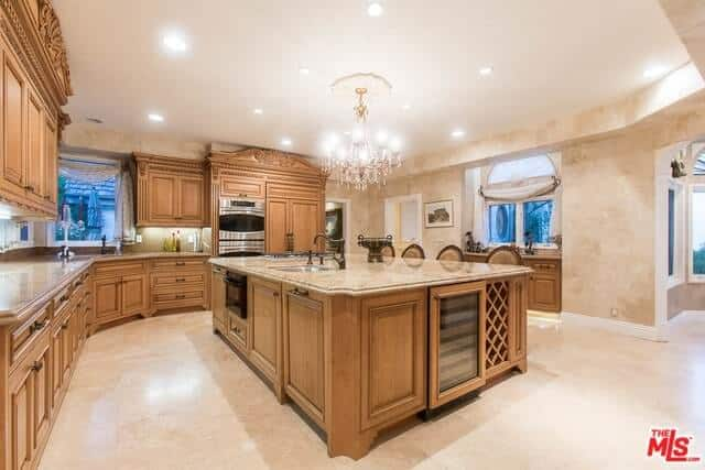 This kitchen features a wooden kitchen island lightens by a stunning chandelier. It also has wooden cabinetry and a white ceiling with lights.