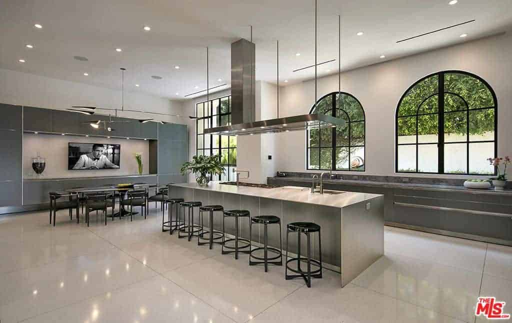 Massive modern kitchen with long island with seating for six and plenty of aisle space around it. The island contains both range and sink. In-kitchen dining adjacent to huge built-in cabinetry and entertainment wall.