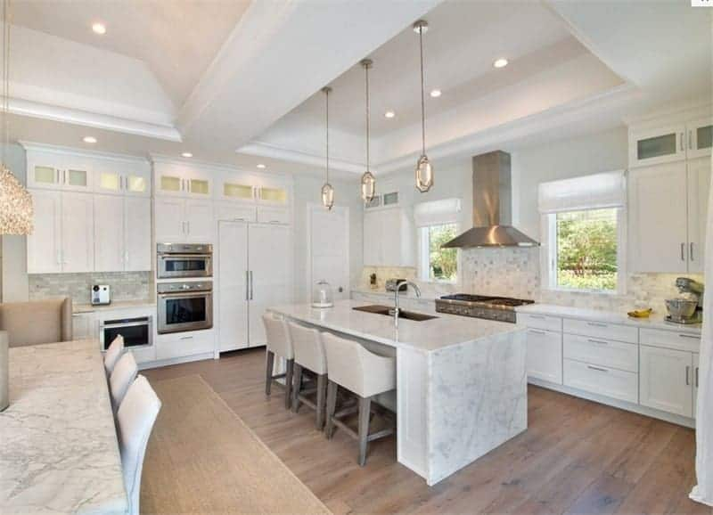 This white kitchen offers a marble kitchen island on the hardwood flooring and stainless steel appliances.