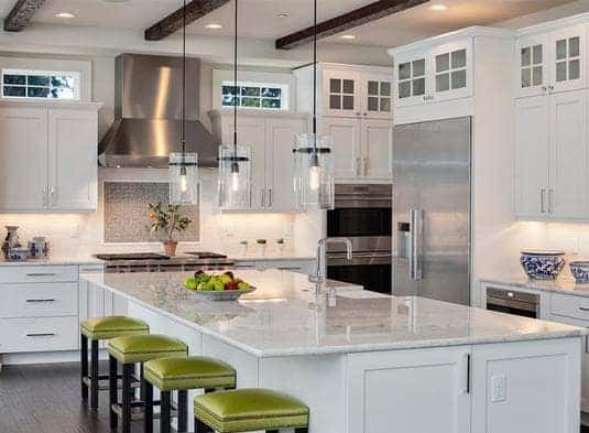 This white kitchen is equipped with a marble top kitchen island lit by pendant light, white cabinetry, and stainless steel appliances.