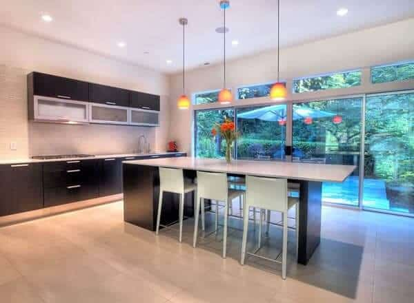 This kitchen offers a dark wood vanity and a kitchen island lit by a pendant light. It has a glass sliding door that leads to the balcony.