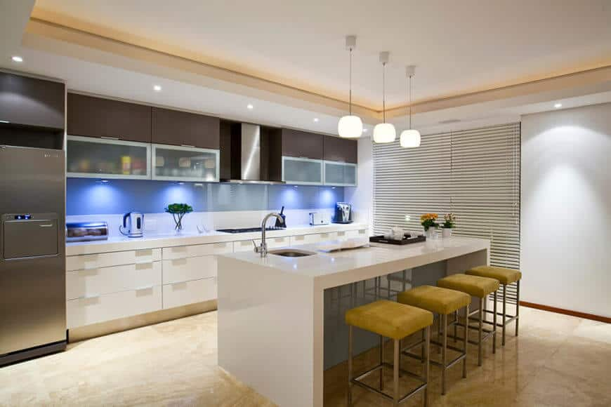 The kitchen is bordered by this large, sleek white island with a built-in sink and plenty of room for barstool dining.