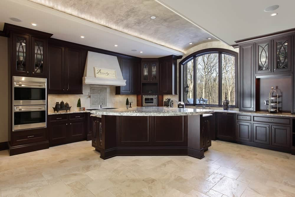 Luxury kitchen with a barrel ceiling, large window, and a massive kitchen island.