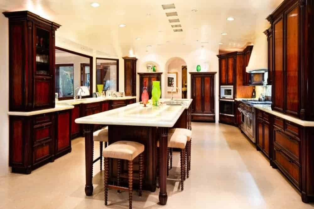 A kitchen with a center island with space for a breakfast bar. This kitchen boasts white marble countertops.