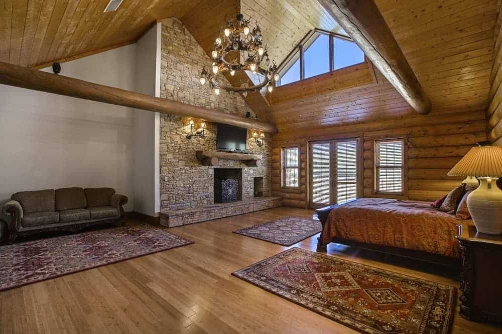 The primary bedroom has a large floor space made of hardwood and adorned with multiple patterned area rugs. There is also a large stone wall housing the fireplace and the wall-mounted TV across from the bed.