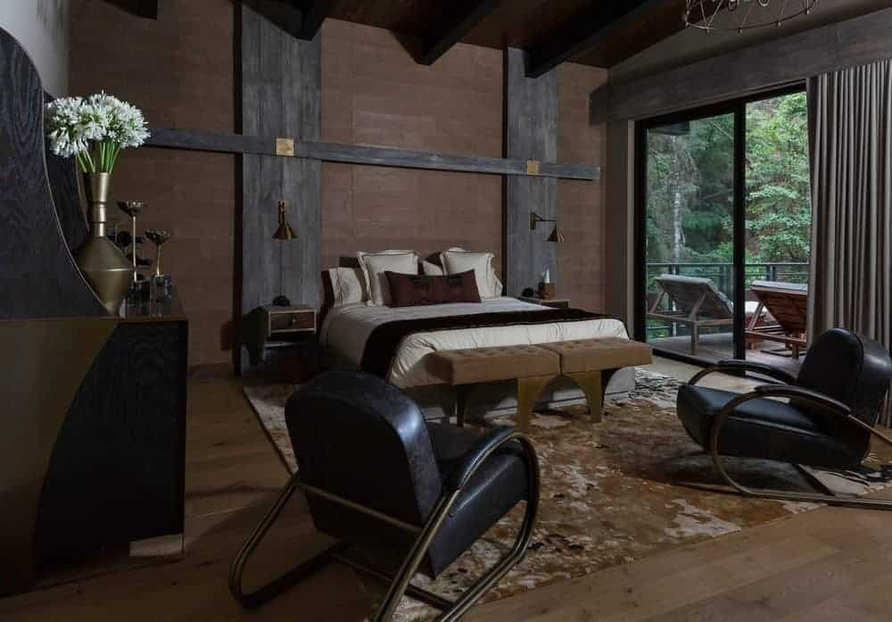 The primary bedroom has a spacious hardwood flooring mostly covered by a large earthy area rug underneath the large bed. The dark wooden ceiling has exposed wooden beams to pair with the couple of black leather arm chairs at the foot of the bed.