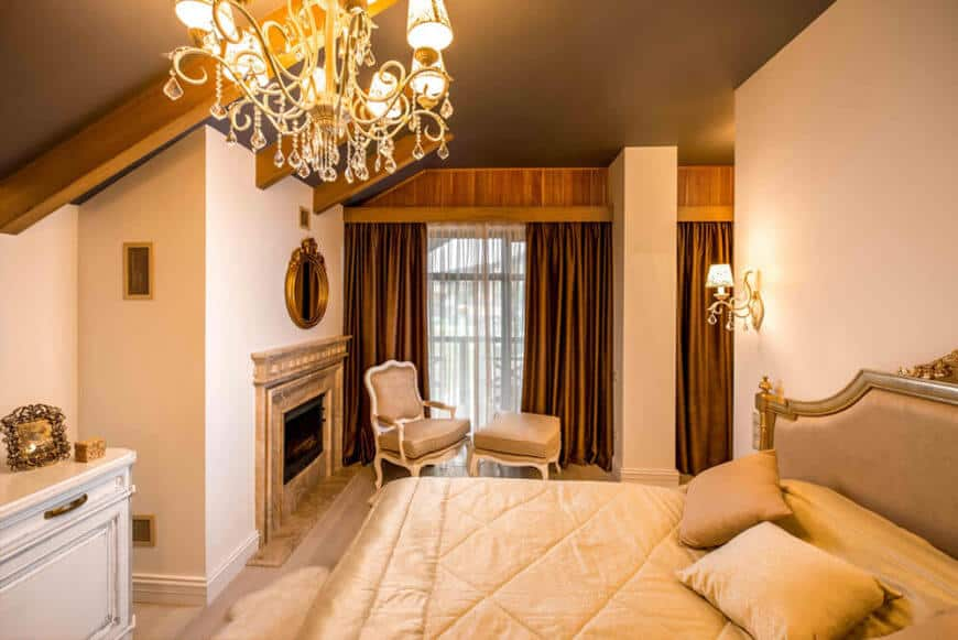 The primary bedroom features a large marble fireplace and relaxing area, all lit via chandelier and wall sconces.