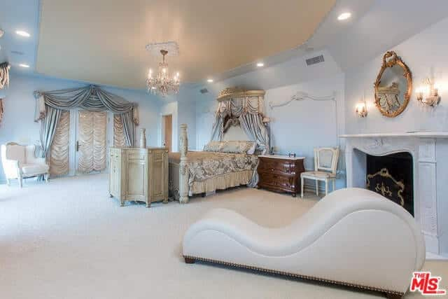 This elegant primary bedroom has a lovely bed style lightens by a sparkling chandelier. It also has a fireplace and a comfy white chair.