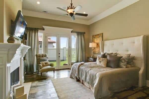 This primary bedroom offers a comfy bed on the stylish rug facing the fireplace and wall-mounted TV. This bedroom has a ceiling fan a glass door that leads to the balcony.