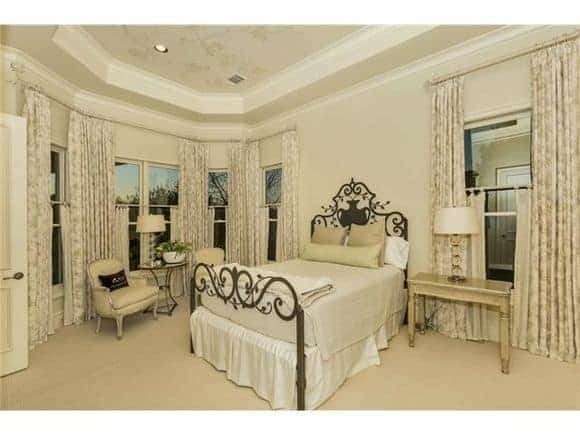 This primary bedroom has an elegant metal bed on carpet flooring and sitting area by the bay window.