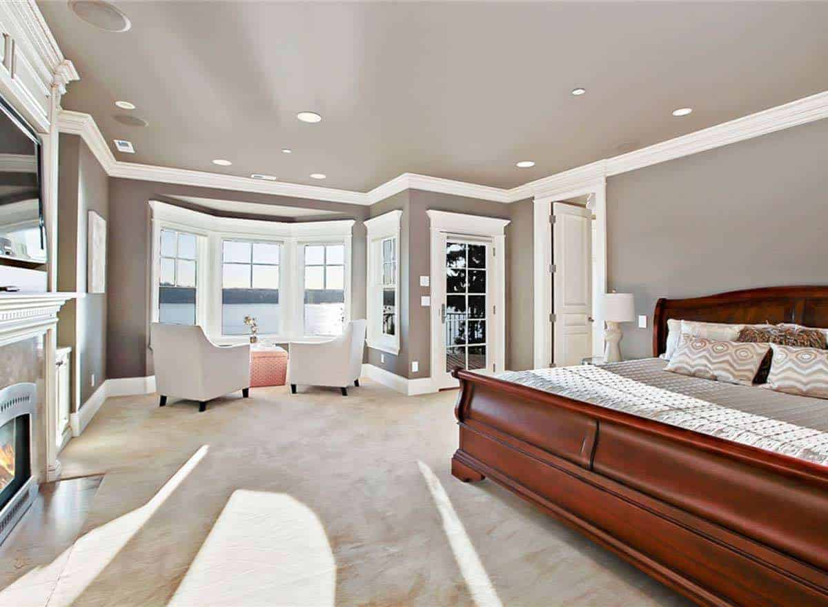 This primary bedroom has a large comfy bed on the stylish carpet flooring. It also has a fireplace and a pair of white chairs in front of windows.